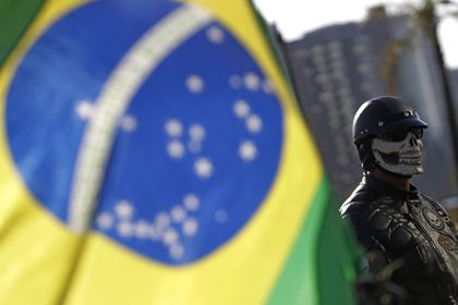 A supporter of Brazil's President Jair Bolsonaro wears a skull mask next to the Brazilian flag before the motorcycle rally with supporters representing the motoclubs in honor of Mother's Day, in Brasilia, Brazil, Sunday, May 9, 2021. (AP Photo/Eraldo Peres)