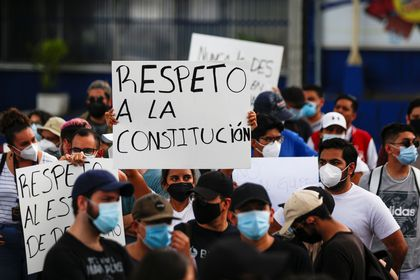 """People hold signs reading """"Respect for the constitution"""", as they protest against the removal of Supreme Court judges and the Attorney General by Salvadoran congress, in San Salvador, El Salvador, May 2, 2021. REUTERS/ Jose Cabezas"""