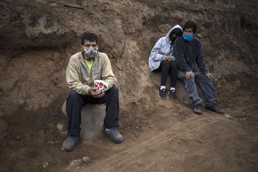 Angel Aguero, left, wearing a mask to curb the spread of the new coronavirus, waits to refill his cup with quinoa donated by a family at the Villa Maria del Triunfo district of Lima, Peru, Wednesday, June 17, 2020.  The food was donated by a wealthy family and distributed in a poverty-stricken area of the capital. (AP Photo/Rodrigo Abd)