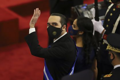 FILE - In this June 1, 2021 file photo, El Salvador's President Nayib Bukele waves during his annual address to the nation to congress, in San Salvador, El Salvador. Bukele's presidency so far is the story of one of Latin America's newest populist autocracies in the making: spending big to hand out goodies, branding opponents as enemies, raising the profile of the military.(AP Photo/Salvador Melendez, File)