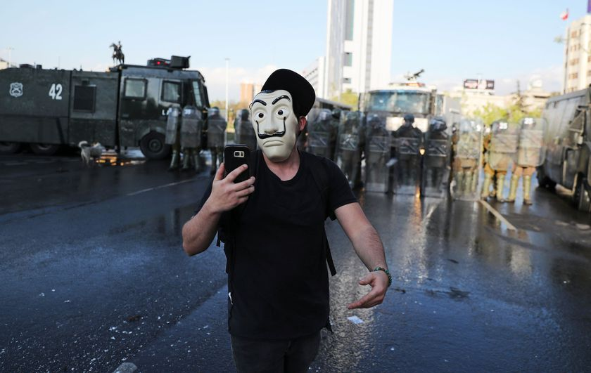 A masked man walks in front of riot police during a protest against Chile's government, in Santiago, Chile October 2, 2020. REUTERS/Ivan Alvarado