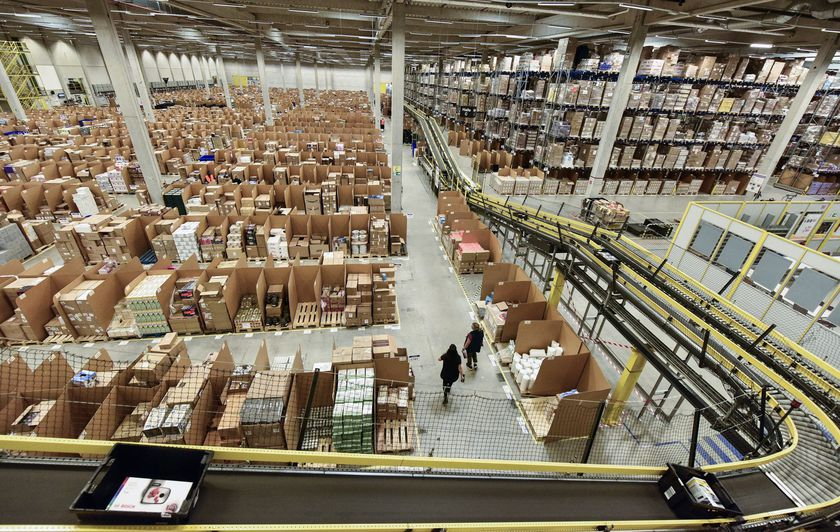 FILE - In this Nov. 14, 2018 file photo, purchase orders leave the giant storehouse of the Amazon Logistic Center in Rheinberg, Germany. Amazon says it's buying 1,800 electric delivery vans from Mercedes-Benz, the biggest such order for the German automaker to date. Mercedes says it will also join a climate initiative established by Amazon's founder Jeff Bezos, committing itself to going completely carbon neutral by 2039. (AP Photo/Martin Meissner)