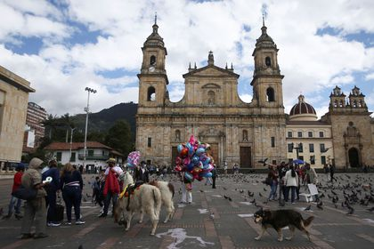 People wearing face masks are seen in the Plaza de Bolivar before the start of a mandatory total isolation decreed by the mayor's office, amidst an outbreak of the coronavirus disease (COVID-19), in Bogota, Colombia January 7, 2021. REUTERS/Luisa Gonzalez