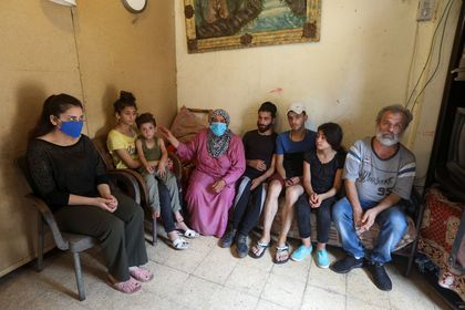 Iman al-Ali sits with her family in a room in Tripoli