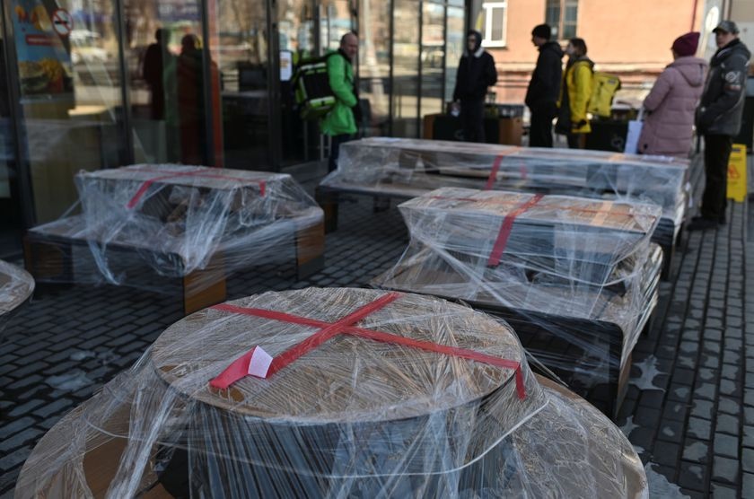 People gather near polythene-wrapped tables outside a McDonald's restaurant in Omsk