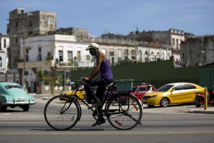 A cyclist wears a face mask amid the new coronavirus pandemic in Havana, Cuba, Monday, Aug. 10, 2020. Cuban authorities on Monday re-imposed measures aimed at containing the spread of COVID-19, restricting inter-provincial travel, closing beaches, bars, restaurants, and keeping the main airport closed to international travel. (AP Photo/Ismael Francisco)