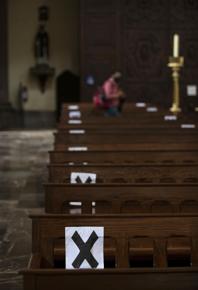 Letter X's mark pews where people should not sit, to create social distancing amid the spread of the new coronavirus, at the Cathedral in Mexico City, Monday, July 20, 2020.  The Catholic church began a gradual reopening of its churches one week ago in the capital and planned to start celebrating Mass again on Monday, but the city asked the church to wait. (AP Photo/Fernando Llano)