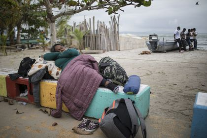 A migrant woman sleeps on a cement bench near the beach in Necocli, Colombia, Thursday, July 29, 2021. Migrants have been gathering in Necocli as they move north towards Panama on their way to the U.S. border. (AP Photo/Ivan Valencia)