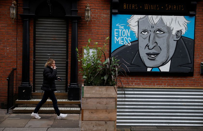 A woman walks past a caricature of Britain's Prime Minister Boris Johnson in the boarded up window of a closed pub in Manchester, Britain, November 10, 2020. REUTERS/Phil Noble       NO RESALES. NO ARCHIVES.