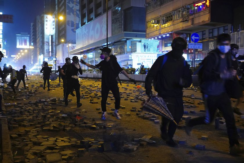Protesters run along a street in the Kowloon area of Hong Kong, Monday, Nov. 18, 2019. As night fell in Hong Kong, police tightened a siege Monday at a university campus as hundreds of anti-government protesters trapped inside sought to escape. (AP Photo/Vincent Yu)