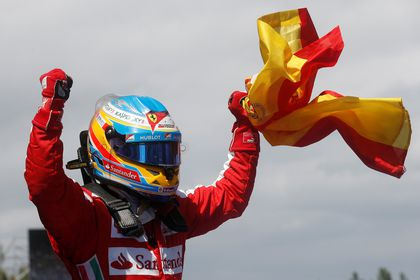 FILE PHOTO: Ferrari driver Fernando Alonso of Spain celebrates holding his national flag after winning the Spanish Grand Prix at the Circuit de Catalunya