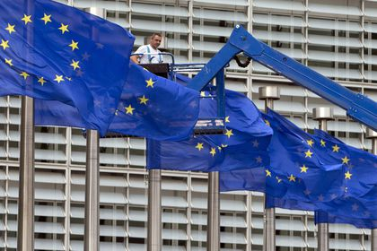 A worker on a lift adjusts the EU flags in front of EU headquarters in Brussels.