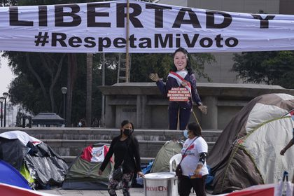 """Supporters of presidential candidate Keiko Fujimori carry a large cooking pot as they camp outside the Palace of Justice, hoping to escalate claims of electoral fraud alleged by Fujimori's campaign one month after the presidential runoff election in Lima, Peru, Monday, July 12, 2021. Supporters of both presidential candidates continue to wait for an official winner of the June 6 election. The sign reads in Spanish """"Freedom. Respect my vote."""" (AP Photo/Martin Mejia)"""