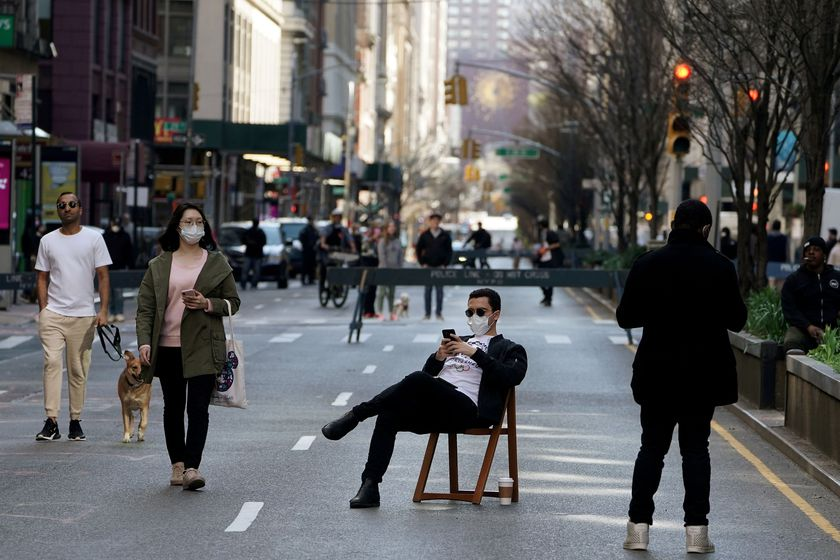 A man sits on a chair as people walk on Park Avenue that was closed to vehicular traffic during the outbreak of coronavirus disease (COVID-19), in the Manhattan borough of New York City