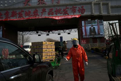 Worker in protective suit holds a thermometer as he checks cars entering the Xinfadi wholesale market, as the country is hit by an outbreak of the novel coronavirus disease (COVID-19), in Beijing