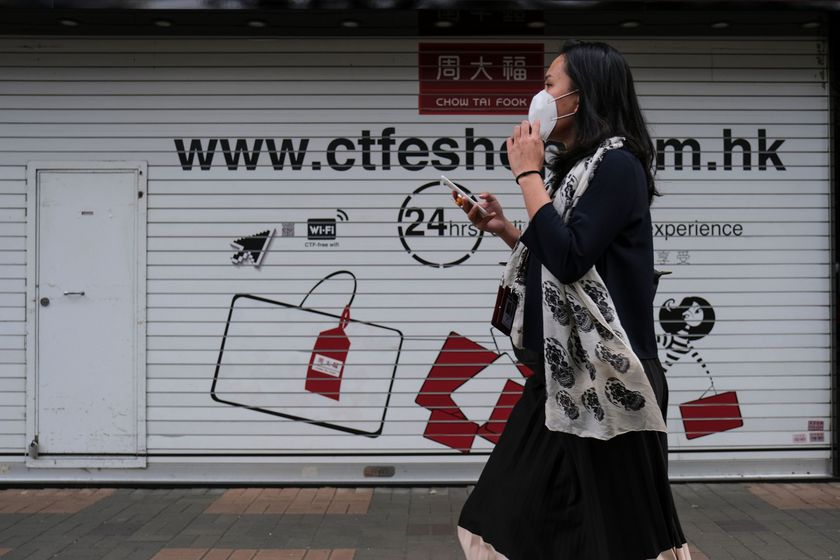 A woman wearing protective mask walks past a closed Chow Tai Fook Jewellery store, following the outbreak of the new coronavirus, in Hong Kong