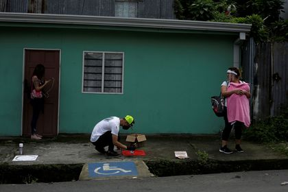 FILE PHOTO: A worker sprays paint on a stencil indicating social distancing on the floor of a bus stop, as the spread of the coronavirus disease (COVID-19) continues, in San Jose, Costa Rica July 24, 2020. REUTERS/Juan Carlos Ulate/File Photo