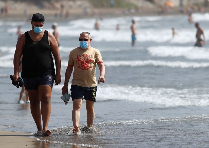 FILE PHOTO: Two men walk along the beach wearing face masks, as the regional government of the Canary Islands forbids smoking without maintaining a safe distance