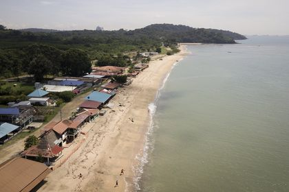 People walk on the shore of a beach one day before beaches officially reopen after months of lockdown to contain the spread of COVID-19, in Veracruz, on the outskirts of Panama City, Friday, Oct. 23, 2020. (AP Photo/Arnulfo Franco)