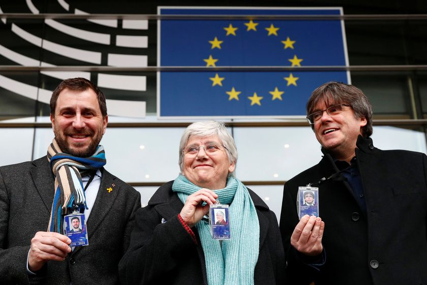 Former members of the Catalan government show their badges outside the EU Parliament in Brussels