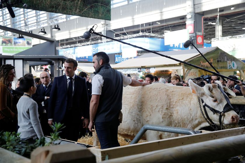 French President Emmanuel Macron speaks with a farmer during a visit to the 57th International Agriculture Fair (Salon international de l'Agriculture) at the Porte de Versailles exhibition center in Paris