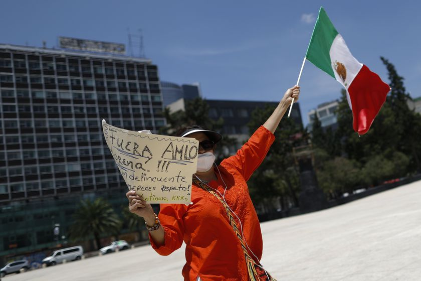 A demonstrator holds up a sign calling for the resignation of President Andres Manuel Lopez Obrador, as she stands along the road during a anti-government driving protest by hundreds of cars, in Mexico City, Sunday, June 28, 2020. (AP Photo/Rebecca Blackwell)