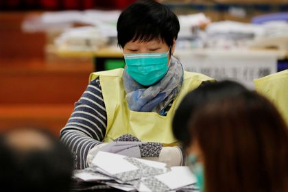 A polling official counts votes of the Hong Kong council elections, in a polling station in Hong Kong
