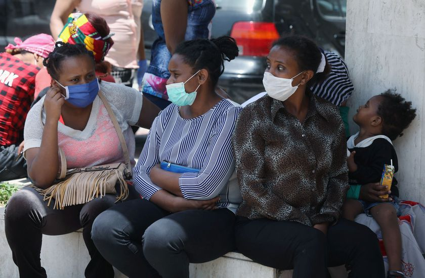 Ethiopian domestic workers wearing masks sit together with their belongings in front of the Ethiopian consulate in Hazmiyeh