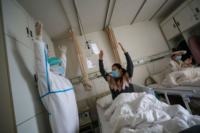 Medical worker in a protective suit shows a patient gestures of an exercise for rehabilitation at a ward of Wuhan Red Cross Hospital in Wuhan
