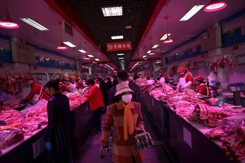 FILE PHOTO: Customers wearing face masks buy pork meat at the Xinfadi wholesale market, as the country is hit by an outbreak of the novel coronavirus disease (COVID-19), in Beijing