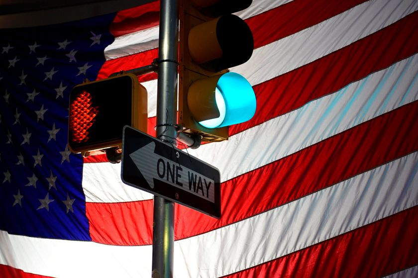 A U.S. flag belonging to a small group of supporters of U.S. President Donald Trump is seen behind a traffic light and a one-way sign, outside the Pennsylvania Convention Center six days after the election in Philadelphia, Pennsylvania, U.S. November 9, 2020. REUTERS/Bastiaan Slabbers