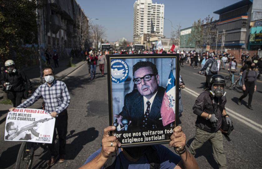 A protester holds a portrait of Chile's late President Salvador Allende during protests marking the anniversary of the 1973 military coup and subsequent death of Allende, in Santiago, Chile, Friday, Sept. 11, 2020. The coup ousting the democratically elected leader, Allende, began the dictatorship of Gen. Augusto Pinochet. (AP Photo/Esteban Felix)
