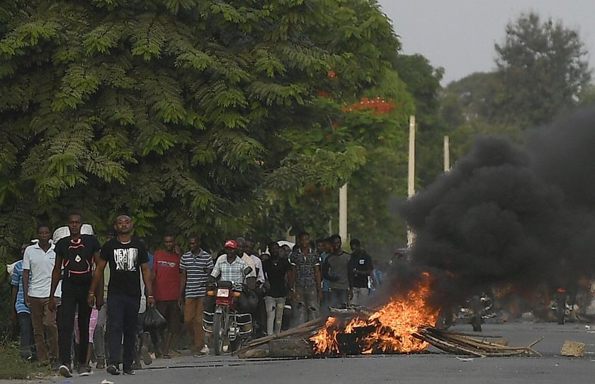 Men walk past a flaming barricade after violence broke out and hundreds of workers fled the area when demonstration near the home town of late President Jovenel Moise grew violent, ahead of his funeral in Quartier Morin, a districto of Cap Haitien, in northern Haiti, Wednesday, July 21, 2021. (AP Photo/Matias Delacroix)