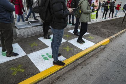 People stand on squares that help for residents to maintain a safe social distance at a bus stop La Reina borough of Santiago, Chile, Tuesday, July 28, 2020. As the Chilean government put in place a roadmap to rolling back on quarantine measures, various neighborhoods in Santiago will begin to ease on the new coronavirus lockdown on Tuesday. (AP Photo/Esteban Felix)
