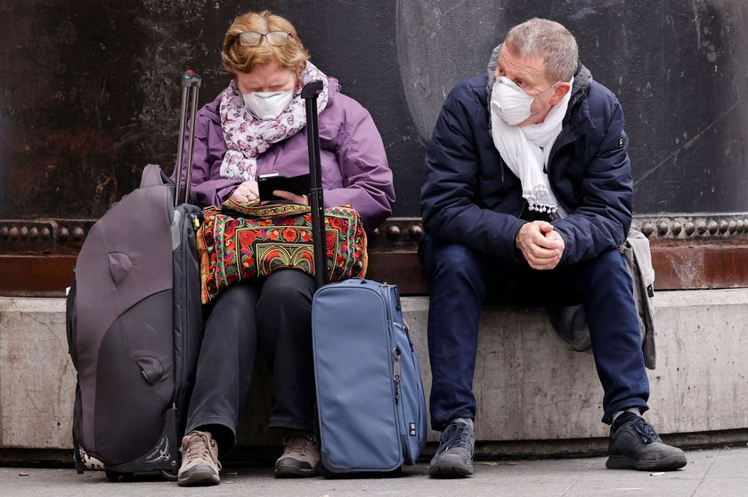 People wearing protective face masks wait in front of Gare du Nord railway station in Paris