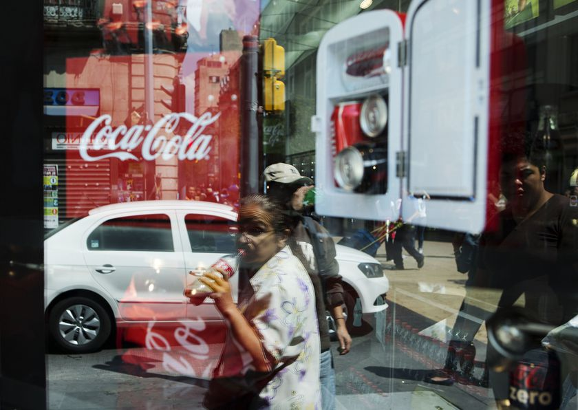 A woman is reflected in a Coca-Cola store window display as she drinks a Coke in Mexico City.