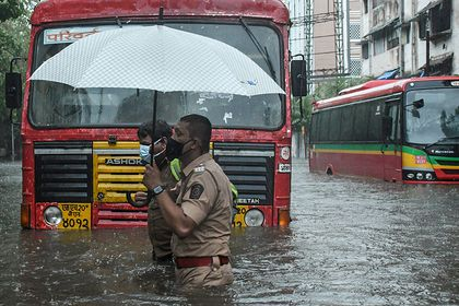 17 May 2021, India, Mumbai: A policeman helps a public transport driver to cross a flooded street due to heavy rain caused by cyclone 'Tauktae' in Mumbai. Photo: Ashish Vaishnav/SOPA Images via ZUMA Wire/dpa Ashish Vaishnav/SOPA Images via  / DPA 17/05/2021 ONLY FOR USE IN SPAIN