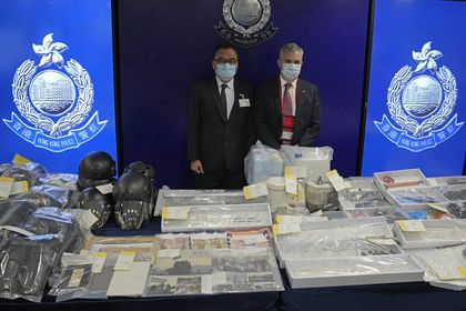 Senior Superintendent Li Kwai-wah, left, of Hong Kong Police National Security Department, and senior bomb disposal officer Alick McWhirter, right of Explosive Ordnance Disposal Bureau, pose with the confiscated evidence during a news conference as nine people were arrested over the alleged plot to plant bombs around Hong Kong, at the police headquarters in Hong Kong, Tuesday, July 6, 2021.(AP Photo/Kin Cheung)