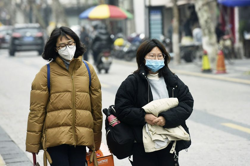 Women wear face masks as they walk down a street in Hangzhou in eastern China's Zhejiang province, Tuesday, Jan. 21, 2020. Face masks sold out and temperature checks at airports and train stations became the new norm as China strove Tuesday to control the outbreak of a new coronavirus that has reached four other countries and territories and threatens to spread further during the Lunar New Year travel rush. (Chinatopix via AP)