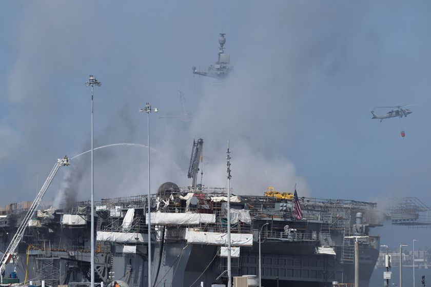 U.S. Navy helicopters and city firefighters continue fighting a fire on the amphibious assault ship USS Bonhomme Richard at Naval Base San Diego