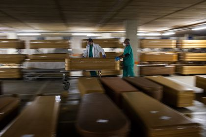 Workers move a coffin with the body of a victim of coronavirus as others coffins are stored waiting burial or cremation at the Collserola morgue in Barcelona, Spain, Thursday, April 2, 2020. The new coronavirus causes mild or moderate symptoms for most people, but for some, especially older adults and people with existing health problems, it can cause more severe illness or death. (AP Photo/Emilio Morenatti)