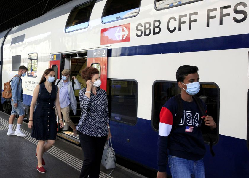 FILE PHOTO: Passengers wear protective masks as they leave a train of Swiss railway operator SBB in Zurich, Switzerland
