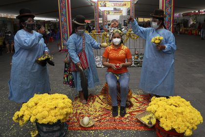 """Shamans use flowers and food to perform a cleansing ritual for Brigite Garces for about a $10 dollar fee at the """"Mercado de Deseos,"""" or Market of Wishes which sets up for one week in Lima, Peru, Monday, Dec. 28, 2020. Amid the COVID-19 pandemic this year, people are wishing for good health and work in 2021, as many have been left without either. (AP Photo/Martin Mejia)"""