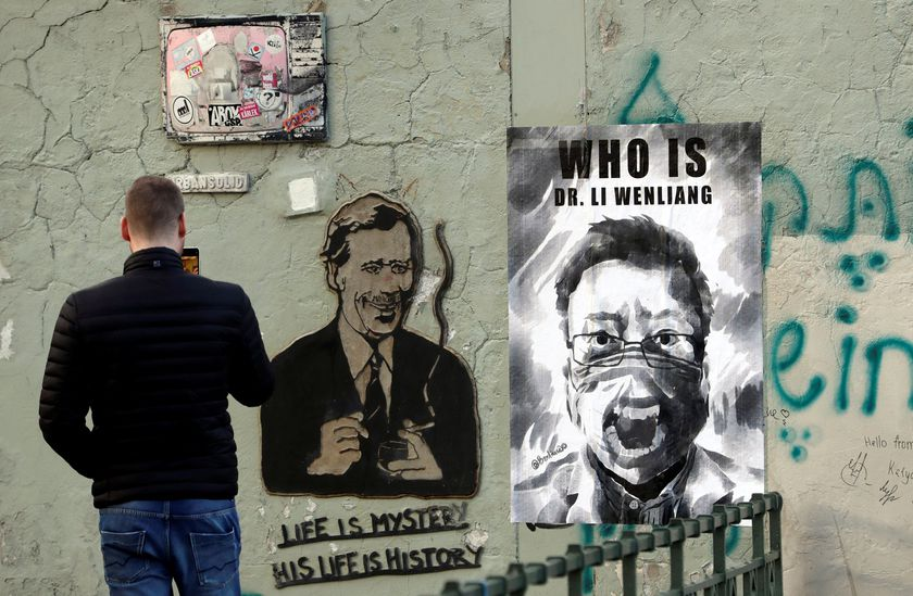 A man takes a picture of a poster of late Li Wenliang in Prague