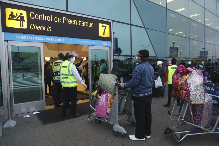 Passengers stand at a distance and wear masks amid the COVID-19 pandemic as they wait in line to check-in at the Jorge Chávez International Airport in Callao, Peru, Wednesday, July 15, 2020. Airports across Peru reopened on Wednesday, serving only domestic flights after closing four months prior. (AP Photo/Martin Mejia)