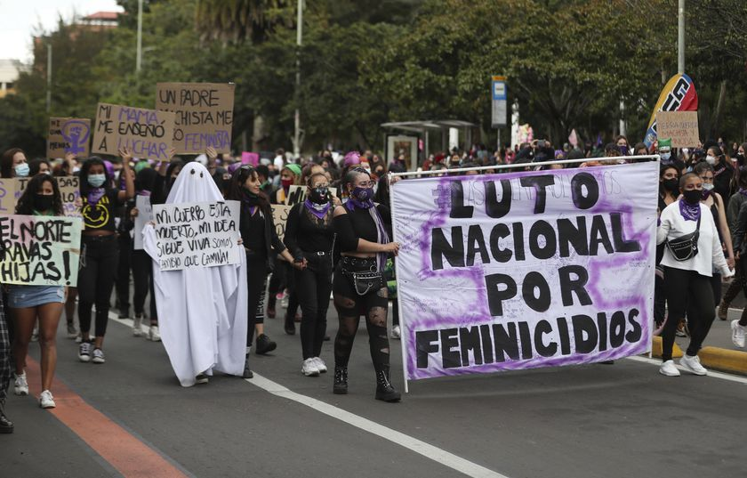 """Activists march with a banner that reads in Spanish """"National mourning because of femicides,"""" during International Women's Day in Bogota, Colombia, Monday, March 8, 2021. (AP Photo/Fernando Vergara)"""