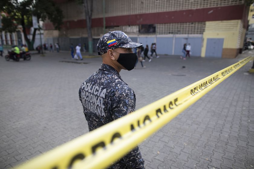 A police officer blocks pedestrian access to a street due to the new coronavirus lockdown in the Catia neighborhood of Caracas, Venezuela, Wednesday, April 7, 2021. (AP Photo/Ariana Cubillos)