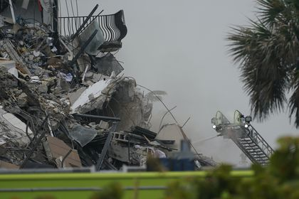 Firefighters use a ladder hose as smoke comes out of the rubble of a partially collapsed building, Thursday, June 24, 2021, in Surfside, Fla. (AP Photo/Wilfredo Lee)
