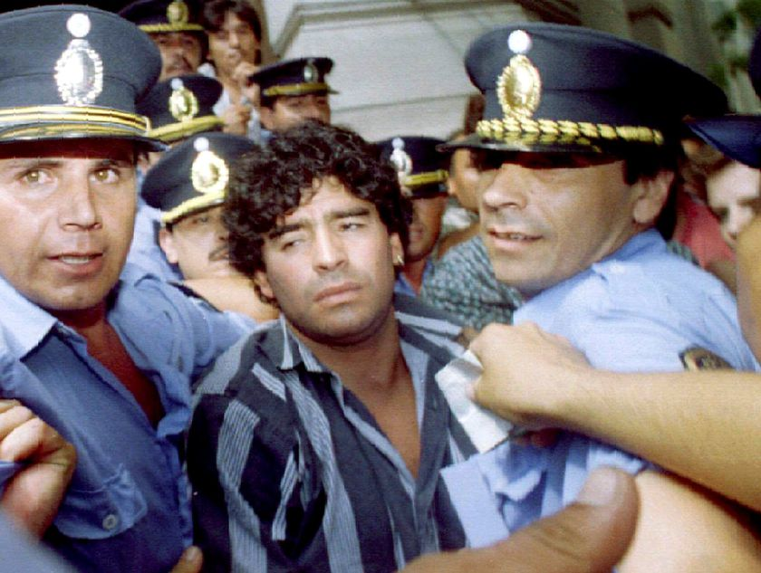 FILE PHOTO: A file photo shows Argentine soccer legend Diego Maradona (C) escorted by police as he leaves a courthouse after answering charges he shot and injured journalists outside his country home two months earlier, in the city of Mercedes 100 kilometers from Buenos Aires, March 15, 1994. REUTERS/File Photo