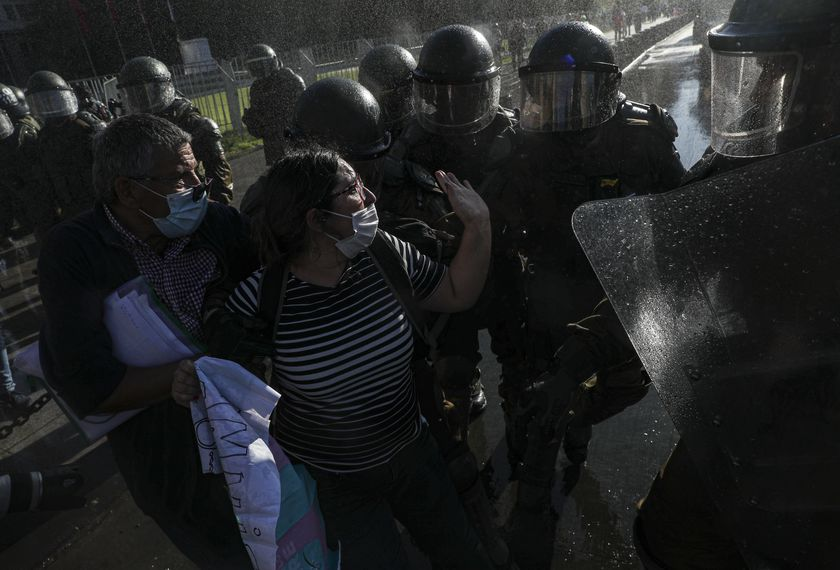 A couple of demonstrators scuffle with police outside of La Moneda presidential palace during a protest against President Sebastian Pi��era, demanding his resignation, in Santiago, Chile, Wednesday, Nov. 18, 2020. (AP Photo/Esteban Felix)